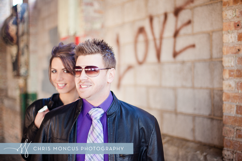 Newlywed couple standing in front of LOVE graffiti on a block wall
